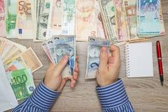 Banquier comptant vrai brésilien à sa table de bureau, Photo stock