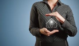 Banquier de femme d'affaires se tenant à la maison dans des mains Images libres de droits
