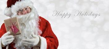 Banret storleksanpassade inage med Santa Claus som rymmer en gåva royaltyfria bilder