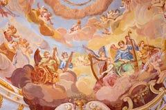 Banska Stiavnica -壁画细节在圆屋顶的在巴洛克式的受难象天使中间教会里与乐器的 库存图片