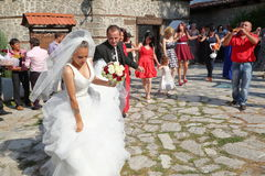 """BANSKO, †de BULGÁRIA """"25 de julho de 2015: Um par do casamento com os convidados que dançam fora da igreja Imagens de Stock Royalty Free"""