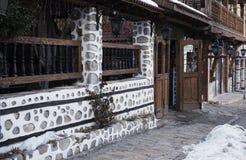 Bansko, Bulgária? 27 de janeiro de 2016 - rua do inverno da neve na cidade de Bansko com casas antigas Casa de pedra Visita do re Imagem de Stock Royalty Free