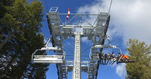 Skiers and snowboarders riding up ski lift, transporting to top of mountain slopes stock photo