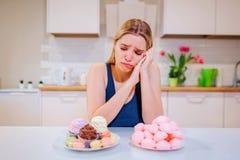Banta ansträngning Den unga ledsna kvinnan i blå T-tröja väljer mellan grönsaker för ny frukt eller sötsaker, medan se dem in royaltyfri fotografi