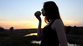 Banta att äta av gravida kvinnan - att äta det gröna äpplet på solnedgången lager videofilmer