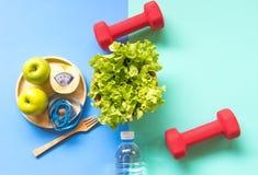 Banta bantningvikt med det gröna äpplet och mätaklappet, skalavikt på den wood plattan, grönsaker, hantlar, färgglad backgrou royaltyfri bild