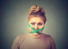 Banta begränsningsspänningen Frustrerad kvinna med att mäta bandet runt om hennes mun royaltyfria foton