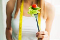 Banta begrepp, den härliga unga kvinnan som väljer mellan sund mat, och skräpmat royaltyfri foto