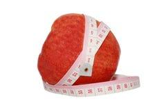 Banta begreppet av det röda äpplet med mäter tejpar Arkivfoton