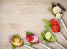 Banta begreppet av skedar med skivade grönsaker på träbräde arkivfoto