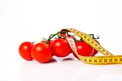 Banta begreppet för viktförlust med måttband organiska tomater med Fotografering för Bildbyråer