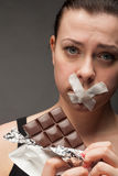 Banta begreppet: kvinna som rymmer en choklad med munnen förseglad royaltyfri foto