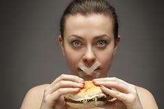 Banta begreppet: kvinna som rymmer en hamburgare med munnen förseglad arkivfoto