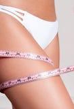 Banta begreppet, kvinnan som mäter hennes ben med ett måttband Arkivfoto