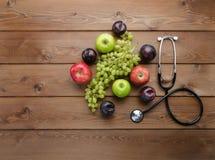 Banta begreppet med den medicinska stetoskopet och nya frukter Fotografering för Bildbyråer