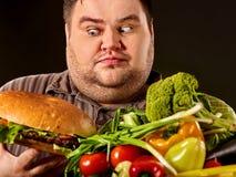 Banta den feta mannen gör val mellan sund och sjuklig mat royaltyfri foto