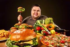 Banta den feta mannen gör val mellan sund och sjuklig mat royaltyfri fotografi