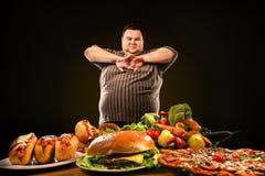 Banta den feta mannen gör val mellan sund och sjuklig mat royaltyfri bild
