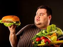 Banta den feta mannen gör val mellan sund och sjuklig mat arkivbilder