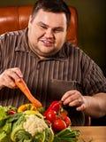 Banta den feta mannen som äter sund mat Sund frukost med grönsaker royaltyfria foton