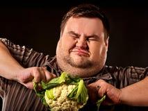 Banta den feta mannen som äter sund mat Sund frukostgrönsakblomkål Royaltyfria Bilder