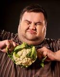 Banta den feta mannen som äter sund mat Sund frukostgrönsakblomkål arkivfoto