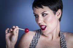 Banta den lyckliga unga kvinnan med lollypop i hennes mun på blått tillbaka Royaltyfri Fotografi