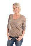 Banta den trevliga le äldre kvinnan som isoleras över bärande jeans för vit fotografering för bildbyråer