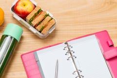 Banta frukosten på skrivbordet med tomt papper och skriva på tabellen arkivfoto
