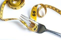 Banta gaffeln med måttband Arkivfoto