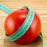 Banta genom att använda rött tomatbegrepp Arkivbild