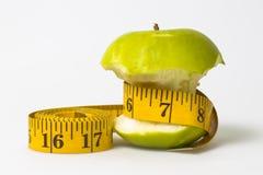 Banta grönt äpple för begrepp med det mätande bandet Royaltyfri Bild