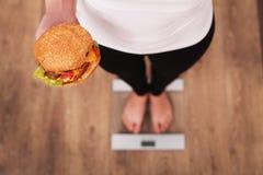 banta Kvinna som mäter kroppsvikt på hamburgaren och äpplet för vägningsskala den hållande Sötsaker är sjuklig skräpmat Att banta royaltyfria foton