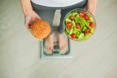banta Kvinna som mäter kroppsvikt på hamburgaren och sallad för innehav för vägningsskala Sötsaker är sjuklig skräpmat banta royaltyfria foton
