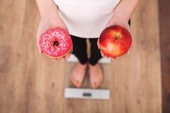 banta Kvinna som mäter kroppsvikt på munken och äpplet för vägningsskala den hållande Sötsaker är sjuklig skräpmat Banta sunda Ea arkivfoto