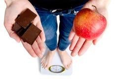 banta Kvinna som mäter kroppsvikt på vägningsskalan som rymmer choklad och äpplet arkivbild