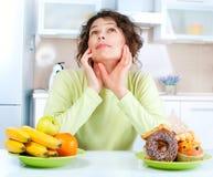 Banta. Kvinna som väljer mellan frukter och sötsaker royaltyfria foton
