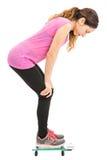 Banta kvinnan som kontrollerar hennes vikt på skala Royaltyfria Foton