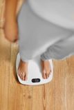 banta Kvinnlig fot på vägningsskala isolerad kvinna för white för vikt för förlustmåtttorso Sund mest lifest Arkivfoto