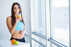 banta Lycklig le ung kvinna som dricker orange fruktsaft arkivfoton