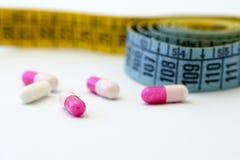 Banta - mäta tejpa och pills royaltyfri fotografi