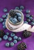 Banta mål. Blackberry och blåbär i en glass krus med mått Royaltyfri Foto