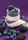 Banta mål. Blackberry och blåbär i en glass krus med mått Fotografering för Bildbyråer