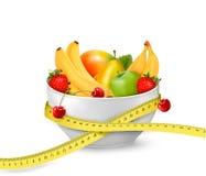 Banta mål. Frukt i en bunke med att mäta bandet. royaltyfri illustrationer
