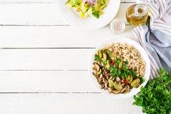 Banta menyn Sunt vegetariskt mål - havregröt för champinjoner shiitake, zucchini- och havremjölpå bunken Strikt vegetarianmat Lek royaltyfri bild