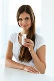 banta näring Härlig le kvinna som inomhus dricker yoghurt fotografering för bildbyråer