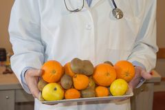 Banta ner att banta begrepp Doktor i det vita labblaget som rekommenderar sund mat Frukter för frukt för innehav för doktorsspeci Arkivfoton