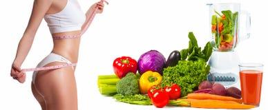 Banta, och den sportiga kvinnan, bantar begrepp med nya grönsaker Royaltyfri Fotografi