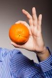 Banta och sund näring Apelsin i den manliga handen Royaltyfri Foto
