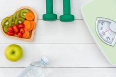 Banta och väga förlust för sund omsorg med sunda viktskalan och konditionutrustning, sötvatten och frukt, royaltyfri foto